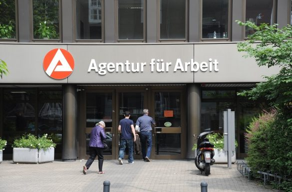 ľudia vchádzajú do budovy nemeckého úradu práce